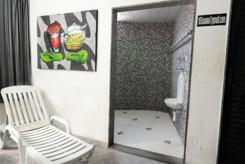 Sala de repouso ao lado sauna com ducha e mictório.